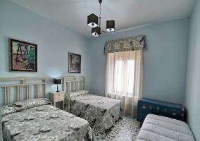 Dormitorio triple en tonos grises y azules