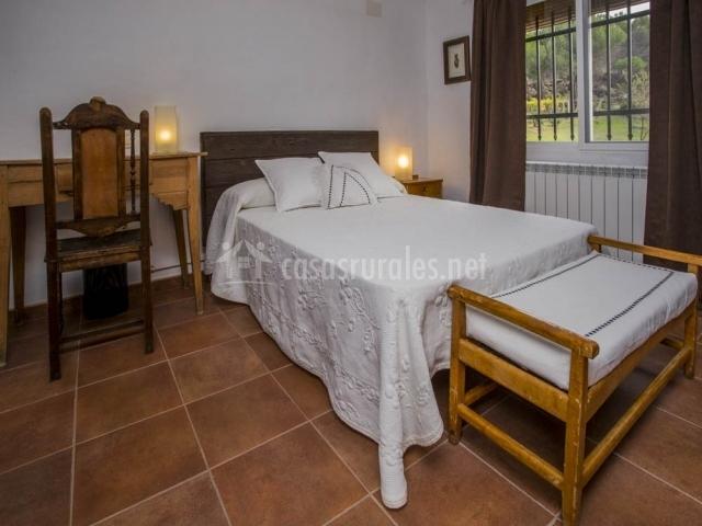 Dormitorio con cama de matrimonio con colcha blanca