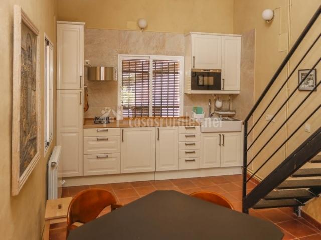 La cocina de la casa con la escalera negra a la derecha
