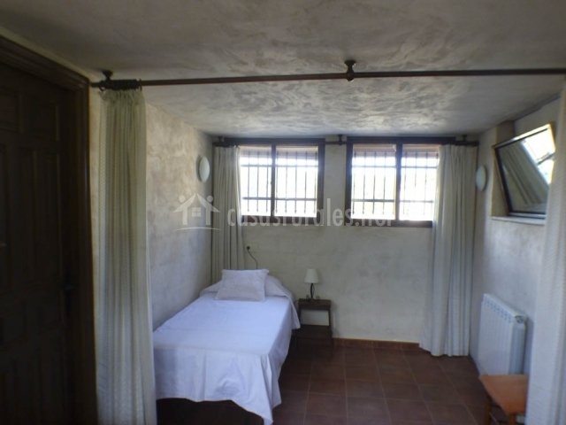 Dormitorio individual con cortinas