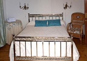 Dormitorio de matrimonio con asiento de mimbre