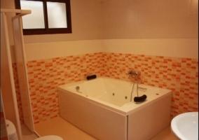 Baño con bañera de hidromasaje y azulejos naranjas