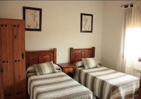 Dormitorio con dos camas individuales y cuadros en la pared