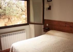 Dormitorio de matrimonio con cabecero alargado de madera