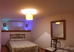 Dormitorio de matrimonio con espejo en un lateral y otra cama