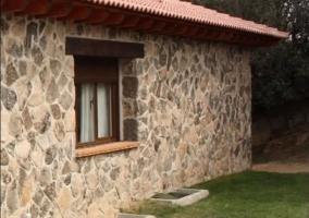 Lateral de la casa con pared de piedras y ventana