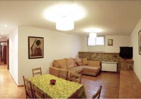 Salón del alojamiento con sillón en L y mesa de comedor
