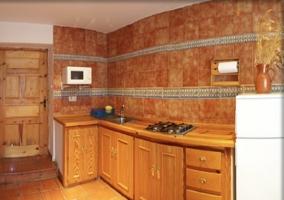 Cocina con encimera de madera y microondas en la pared
