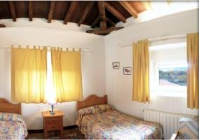 Dormitorio con dos camas individuales y tablones en el techo
