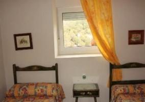 Dormitorio con dos camas y ventana con visillo amarillo