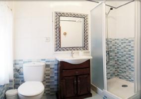 Aseo con mueble de madera en el lavabo y ducha