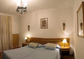 Dormitorio con dos camas y cabecero de madera alargado