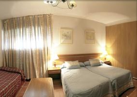 Dormitorio doble con dos camas y otra supletoria