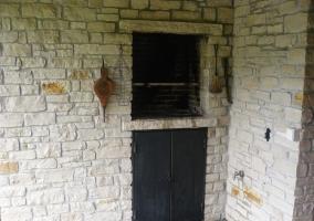 Barbacoa en el patio de la casa entre muros de piedra
