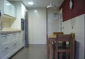 Cocina independiente con muebles blancos y mesa