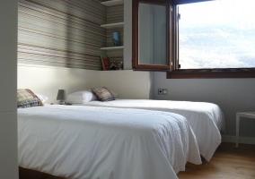 Dormitorio con dos camas individuales y ventanal abierto
