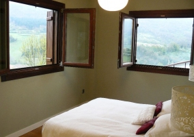 Dormitorio de matrimonio con dos ventanas abiertas