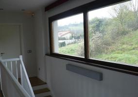 Escaleras al primer piso y ventanal con vistas del paisaje