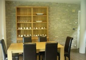 Mesa del comedor con mueble al lado y paredes de piedra