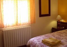 Cama de matrimonio en dormitorio con ropa de ducha