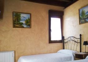 Dormitorio con dos camas y cuadros adornando las paredes