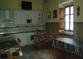 Comedor del alojamiento con mesas y la cocina