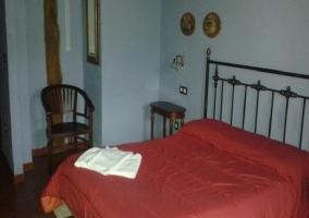 Dormitorio de matrimonio con cama roja y silla al lado