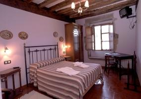 Dormitorio doble con cama de matrimonio y televisor colgado delante