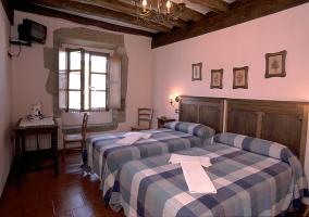 Dormitorio doble con dos camas individuales y televisor colgado