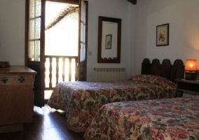 Dormitorio doble con camas individuales con balcón