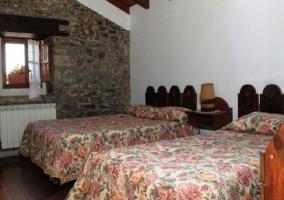 Dormitorio doble con muro de piedra