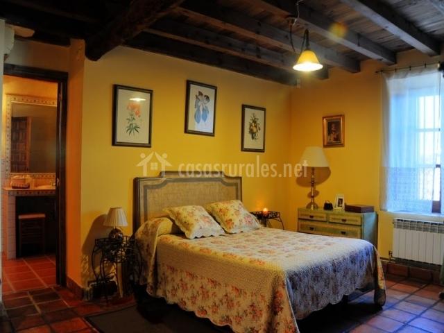 Dormitorio de matrimonio con paredes amarillas y acceso al aseo