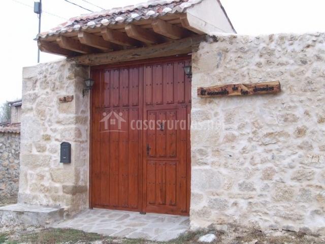 Entrada al alojamiento con muros de piedra y puerta de madera