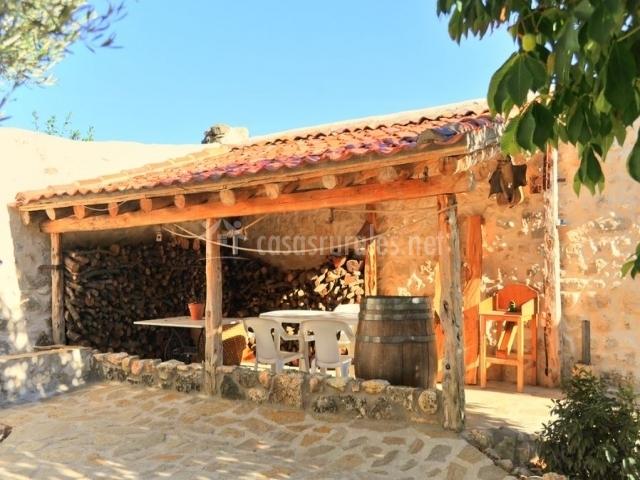 Patio exterior con merendero techado y espacio para guardar la madera