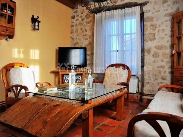 Salón de la casa con mesa baja de madera y cristal encima