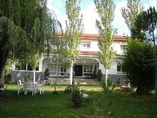 Fachada de la casa con el patio delante y varias plantas