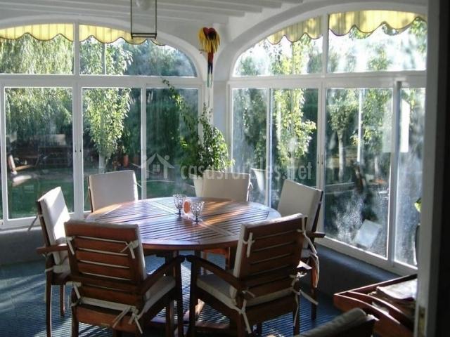 Mesa redonda de comedor con sillas en terraza acristalada