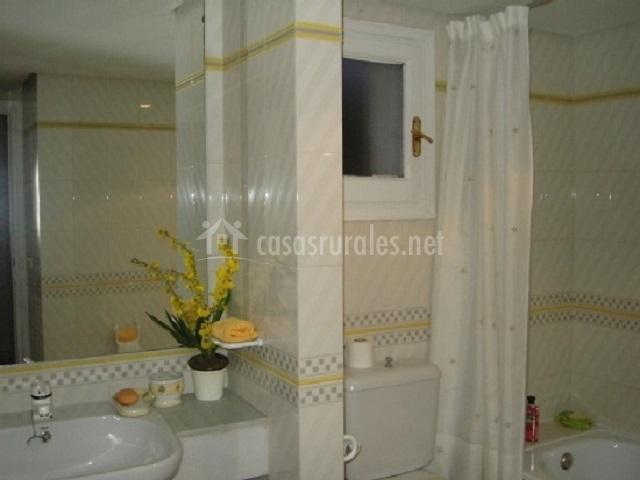 Aseo con lavabo y espejo grande encima y bañera
