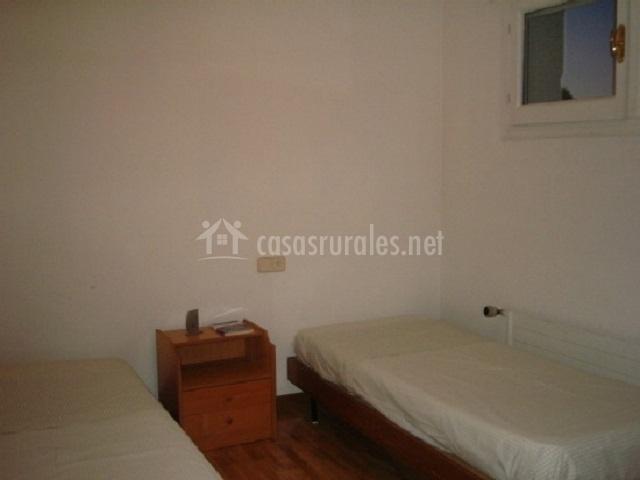 Dormitorio con camas individuales y paredes blancas