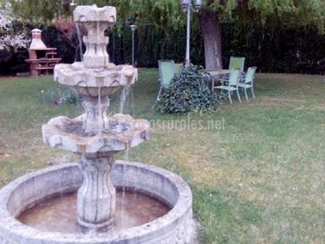 Fuente en el patio ajardinado con barbacoa al fondo