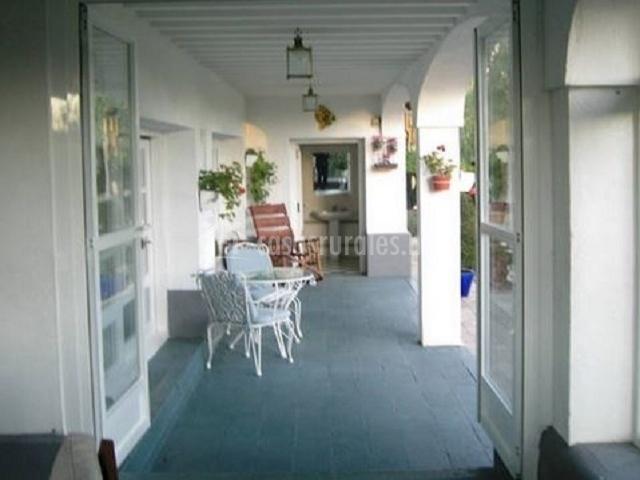 Salida al porche de la casa con muebles de exterior