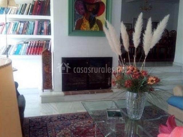 Salón con chimenea frente a mesa baja de cristal