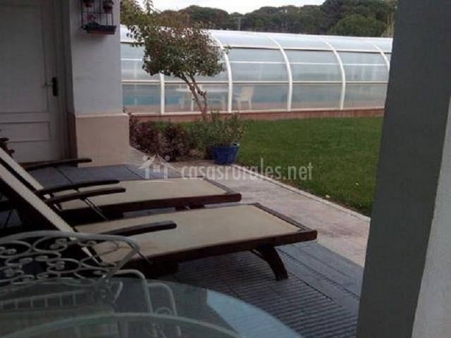 Tumbonas en porche de la casa y piscina cubierta al fondo