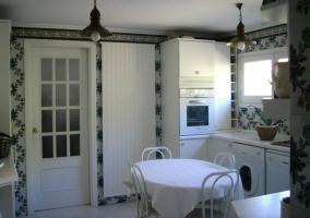 Cocina con paredes y muebles blancos y lavadora frente a mesa