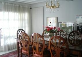 Comedor con una mesa de madera grande y sillas alrededor