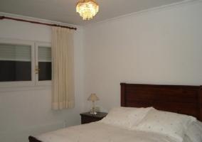 Dormitorio con cama de matrimonio y lámpara de techo encendida