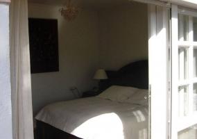 Dormitorio con cama de matrimonio y salida al exterior