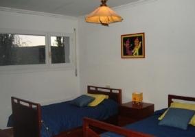 Dormitorio con dos camas azules y cuadros con dibujos