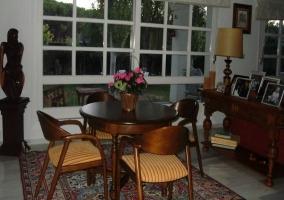 Mesa redonda sobre alfombra al lado de mueble con fotos