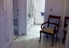 Silla en sala con acceso al aseo con bañera